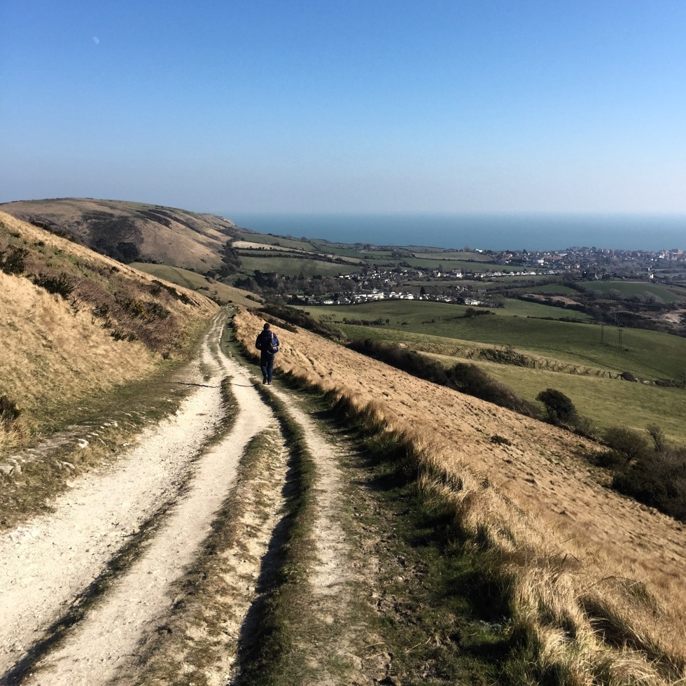 A walker on the Purbeck Way with Swanage in the distance